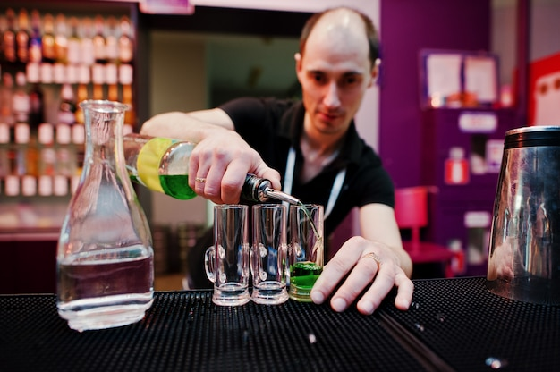 Barman przygotowuje zielony meksykański koktajl w barze