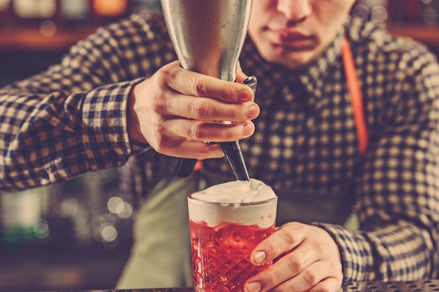 Barman przyrządzający koktajl alkoholowy przy barze w barze