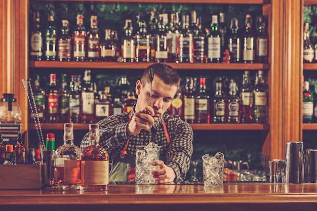 Barman przyrządzający koktajl alkoholowy przy ladzie barowej w przestrzeni barowej