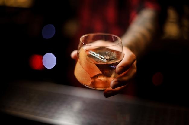Barman ręki trzymającej szklankę whisky dof świeżego koktajlu kapitana jamesa cooka