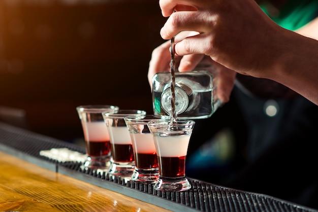 Barman robi kieliszki w nocnym klubie mocnym trunkiem