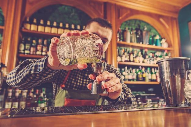 Barman robi koktajl alkoholowy przy barze w barze