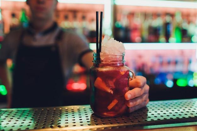 Barman robi koktajl przy marmurowym blacie barowym.
