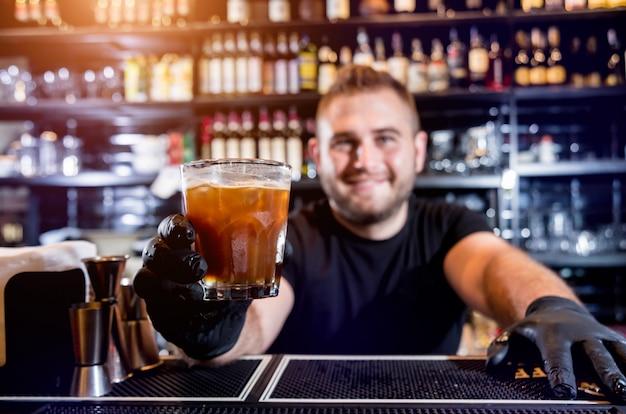 Barman robi koktajl w barze. świeże koktajle. barman w pracy. restauracja. życie nocne.