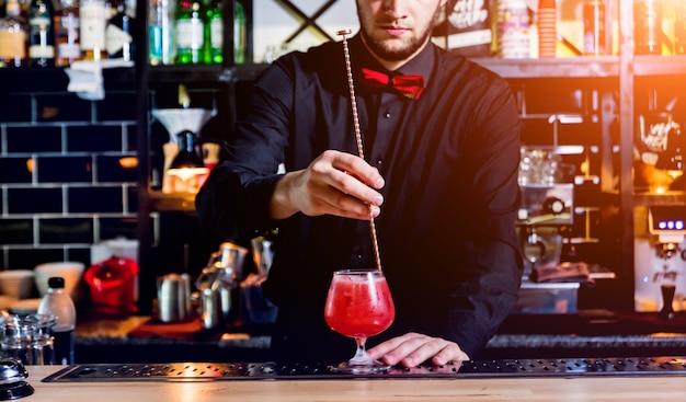Barman robi koktajl w barze. świeże koktajle.