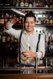 Barman robi koktajl z uśmiechem