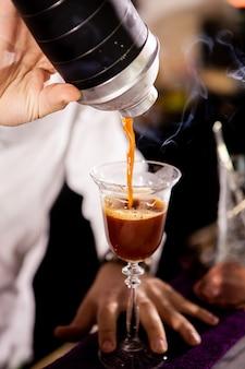 Barman robi napój alkoholowy do kawy. nalewanie napoju
