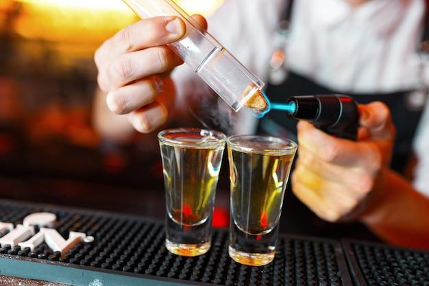Barman robi shoty gorącego alkoholu na barze w pubie z profesjonalnym palnikiem. barman zapala zapalniczkę nad kieliszkiem, zrelaksuj się w nocnym klubie. gorące napoje ogniste. pozwala imprezę