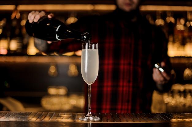 Barman robi świeżego i smacznego francuskiego koktajlu 75