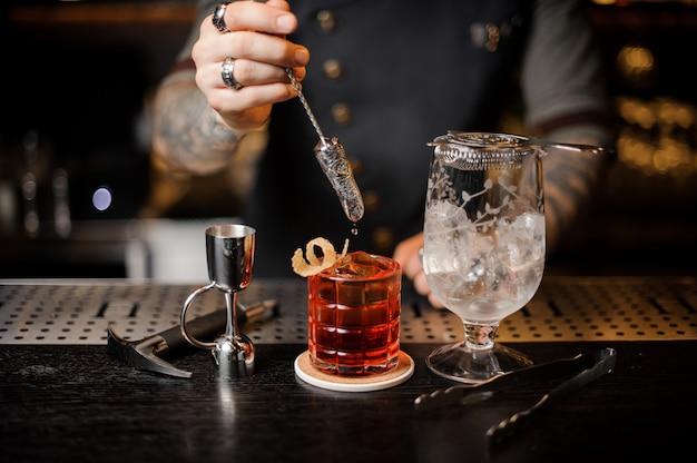 Barman robi świeży i chłodny letni koktajl przy użyciu sprzętu barowego