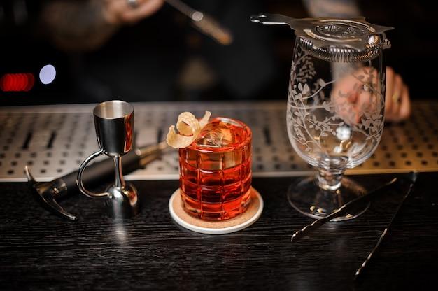 Barman robi świeży i słodki letni koktajl przy użyciu sprzętu barowego