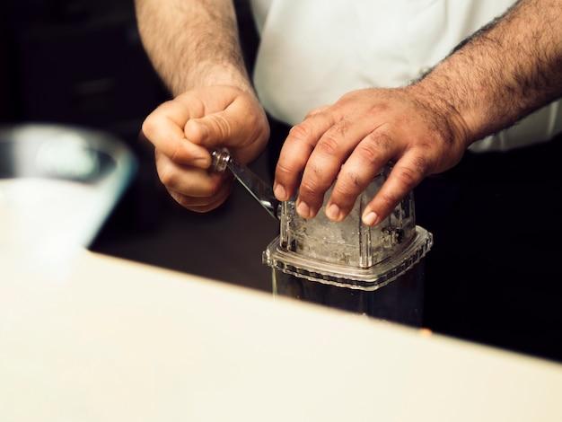 Barman rozbijający lód z wyposażeniem baru