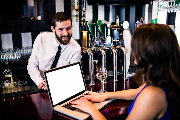 Barman rozmawia z klientem za pomocą laptopa w barze