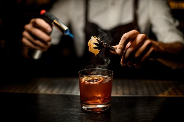 Barman serwujący brązowy koktajl topniejący karmel z palnikiem nad plasterkiem cytryny