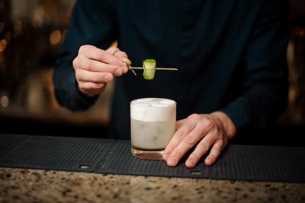 Barman serwujący koktajl z ogórkiem w barze
