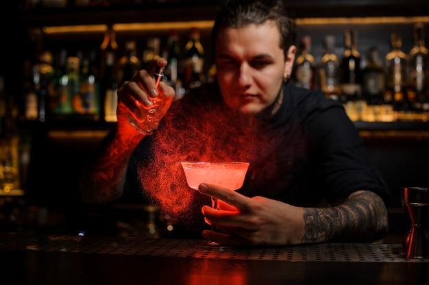 Barman spryskuje pyszny koktajl ze specjalnego waporyzatora w czerwonym świetle na blacie barowym