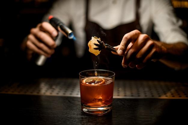 Barman topiący karmel z palnikiem nad kieliszkiem koktajlowym z plasterkiem cytryny w ciemności