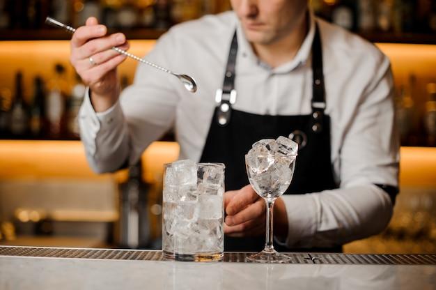 Barman trzyma długą łyżkę i szklankę z kostkami lodu
