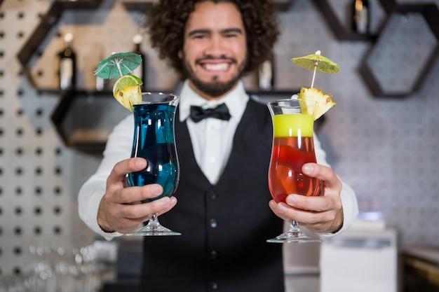 Barman trzyma dwie szklanki koktajlu w barze licznika