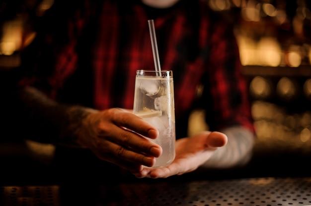 Barman trzyma elegancki kieliszek z długim napojem wypełniony koktajlem toma collinsa