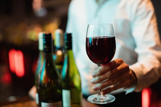 Barman trzyma kieliszek czerwonego wina