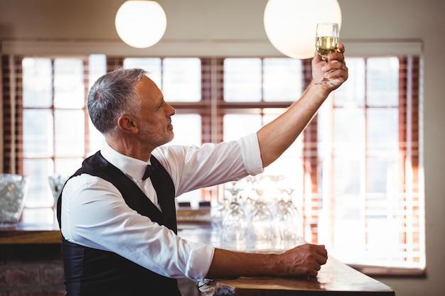Barman trzyma kieliszek do wina w barze