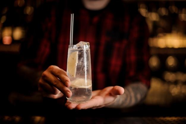 Barman trzyma kieliszek z długim napojem wypełniony koktajlem toma collinsa