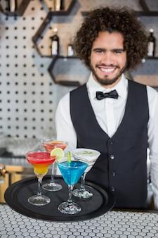 Barman trzyma tacę koktajli i koktajlu mlecznego w barze
