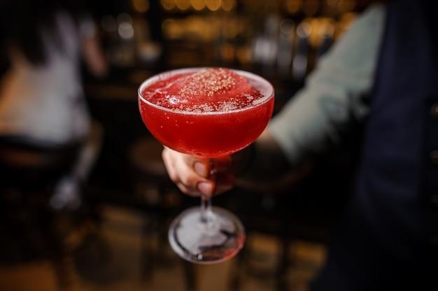Barman trzyma zdobioną szklankę czerwonego koktajlu alkoholowego