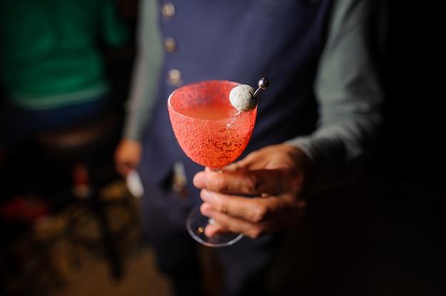 Barman trzyma zdobioną szklankę koktajlu alkoholowego