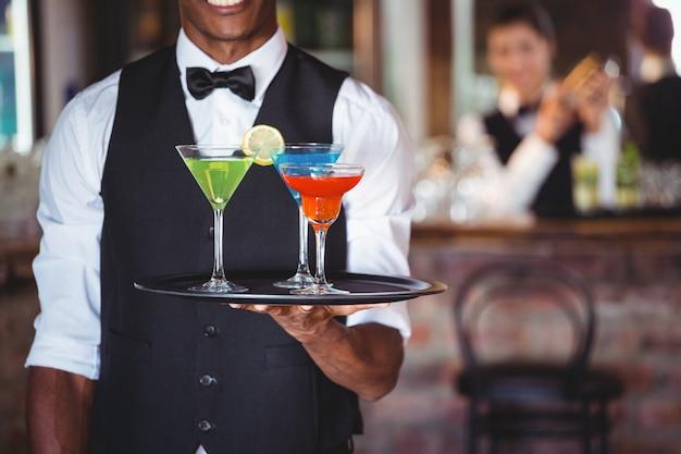 Barman trzymając tacę z kieliszki koktajlowe