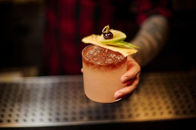 Barman trzymający kieliszek koktajlowy wypełniony smacznym słodkim napojem alkoholowym z lodem i kawałkami owoców na blacie barowym