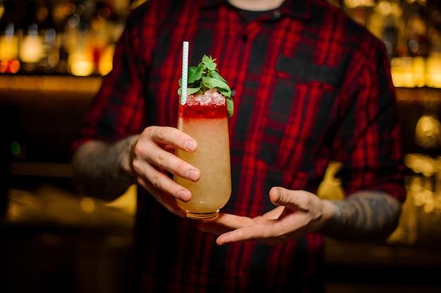 Barman trzymający szklankę kolorowego słodkiego tropikalnego soczystego koktajlu ananasowego z czerwonym likierem ozdobionym listkami mięty