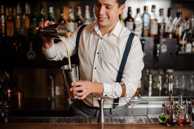 Barman uśmiecha się i miksuje koktajl