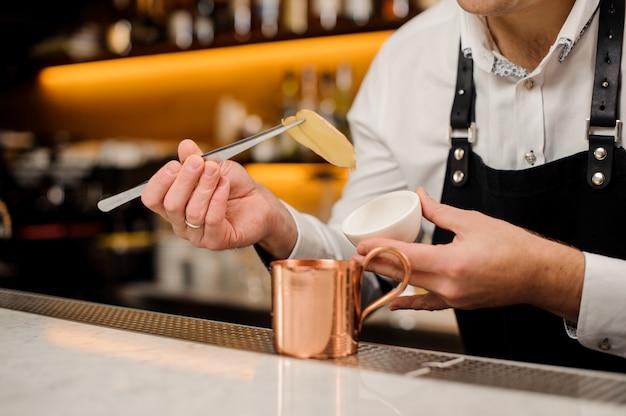 Barman w białej koszuli, dodając do kubka dwa plasterki imbiru