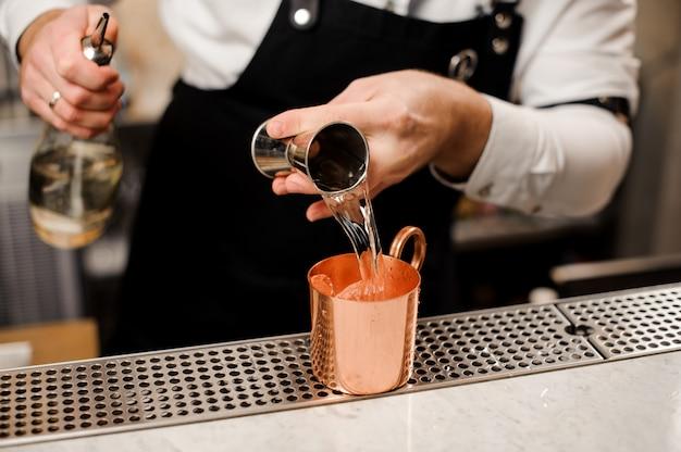 Barman w białej koszuli wlewa porcję napoju alkoholowego do filiżanki