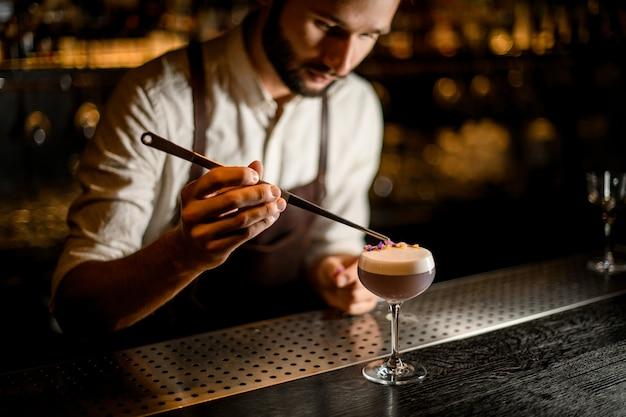 Barman w fartuchu ozdobiony szumowiną jasnofioletowego koktajlu z żółtymi i fioletowymi płatkami