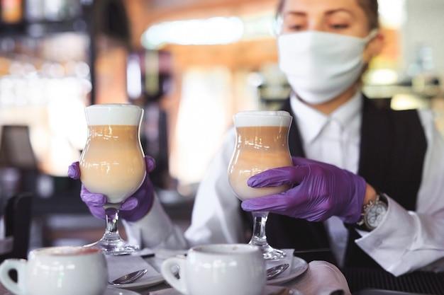 Barman w medycznej masce i rękawiczkach robi kawę latte