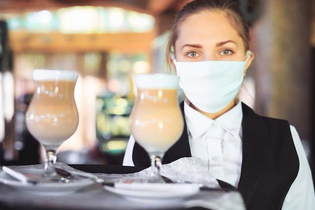 Barman w medycznej masce i rękawiczkach z kawą latte