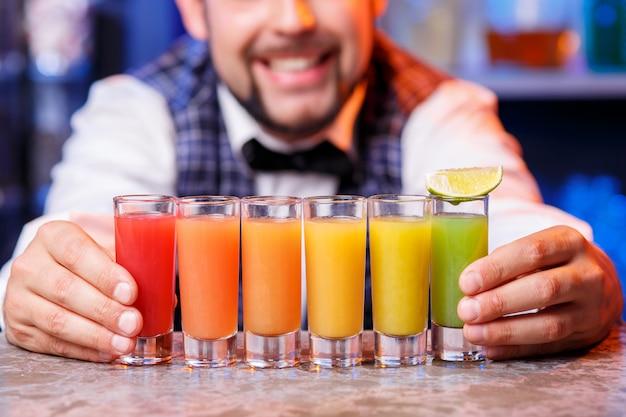 Barman w pracy, przygotowuje koktajle.