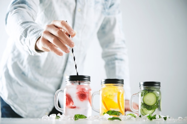 Barman wkłada słomkę w paski ze świeżą zimną domową lemoniadą z lodu, truskawek, pomarańczy, ogórka i mięty.