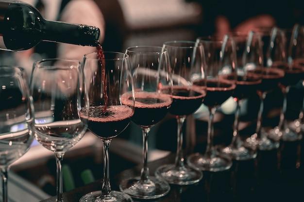Barman wlewając czerwone wino do kieliszka. restauracja, napoje, koncepcja napojów alkoholowych.