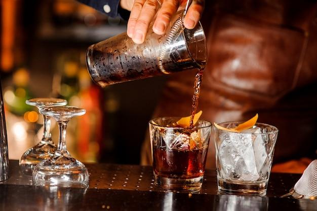 Barman wlewając do szklanek napój alkoholowy
