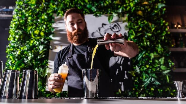 Barman wlewając sok