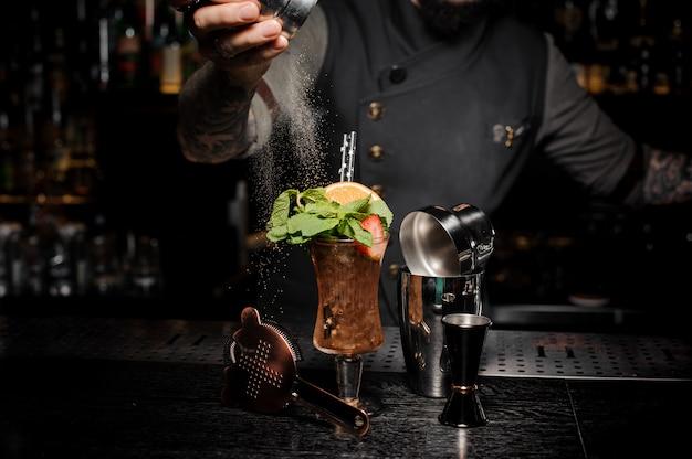 Barman wlewający cukier w mocne i świeże letnie ujęcie