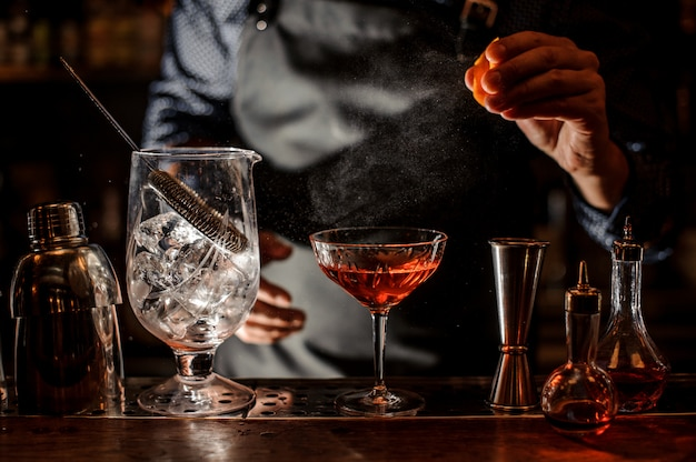 Barman wrzuca do koktajlu świeży sok pomarańczowy