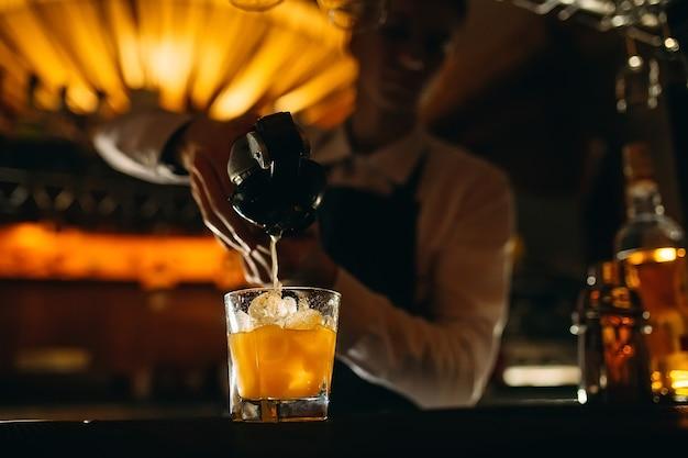 Barman wyciska sok cytrusowy do koktajlu