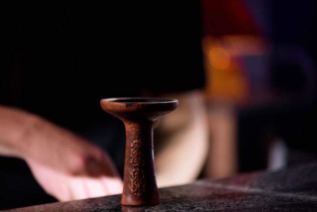 Barman wypełnia czarną, wypaloną ceramiczną miskę do fajki wodnej palącej różne rodzaje tytoniu.