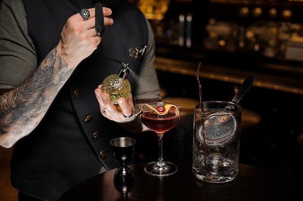 Barman z tatuażem robi świeży i słodki letni koktajl z wiśniami i alkoholem