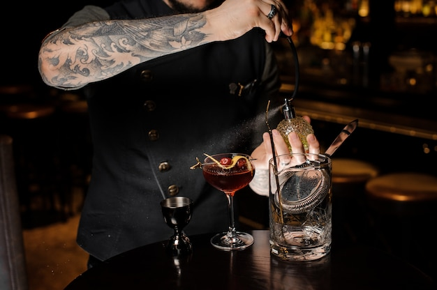 Barman z tatuażem robi świeży i słodki letni koktajl z wiśniami